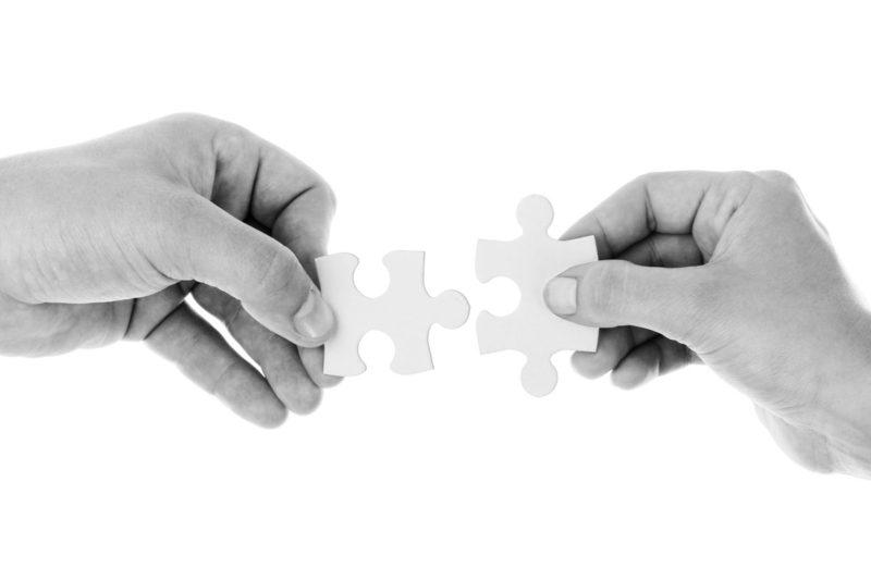 Hände mit zwei Puzzleteilen