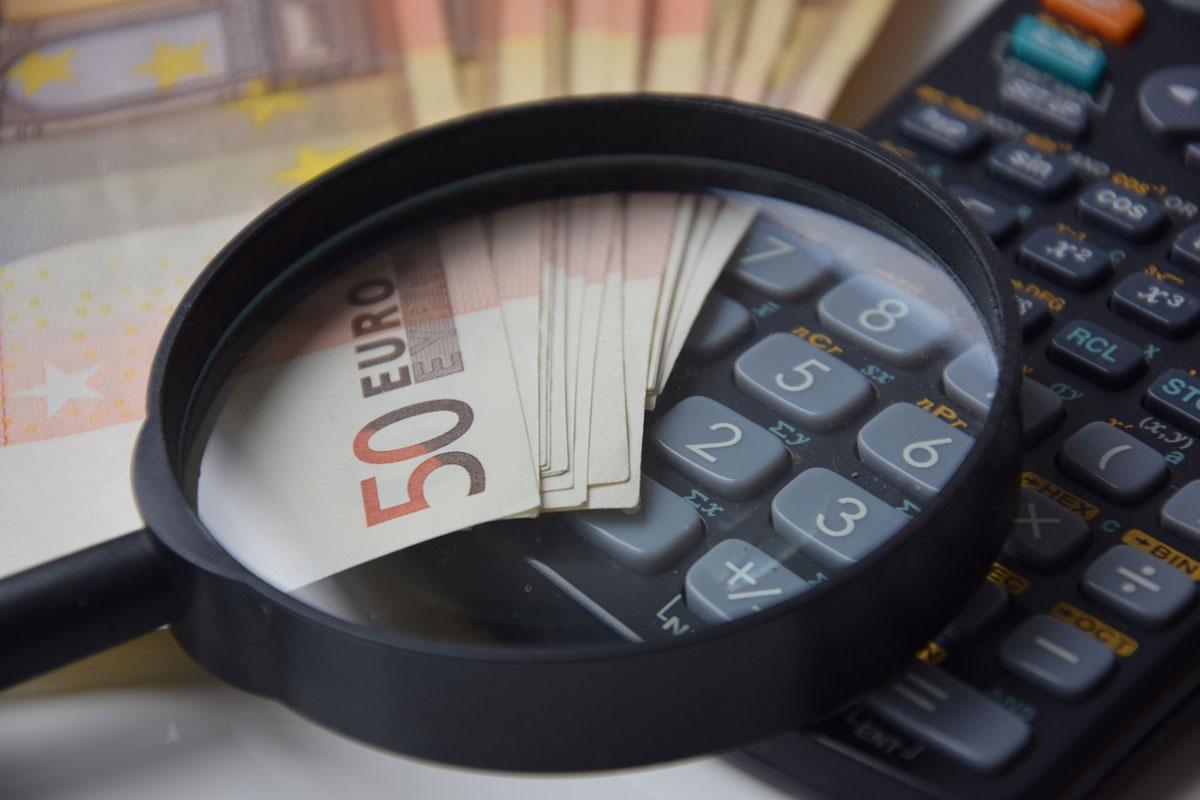 Montage von Lupe, Geldscheinen, Taschenrechner