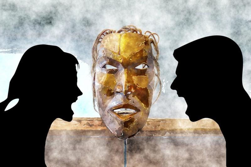 Silhouetten von Mann und Frau, die sich anschreien, vor gemalter Maske