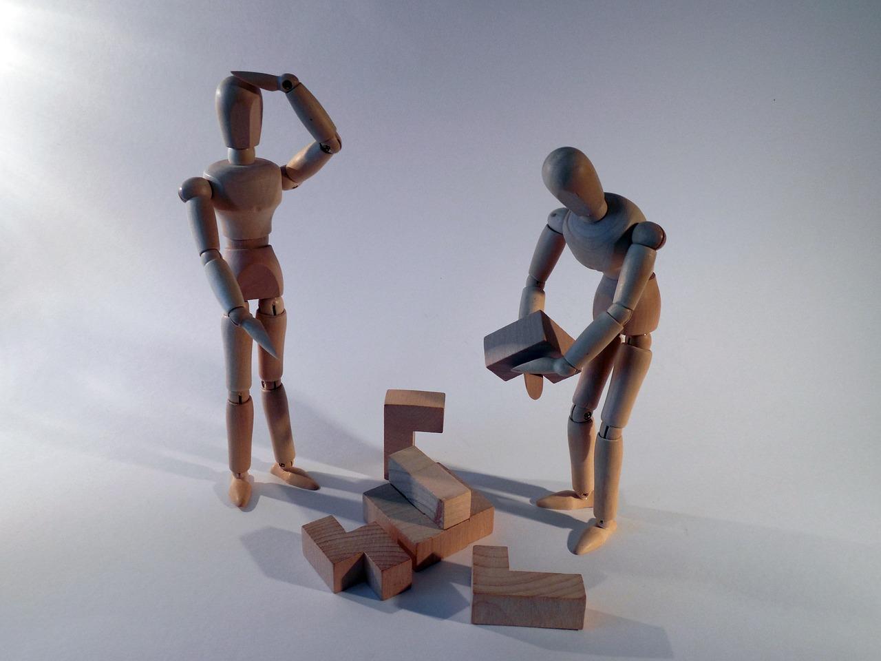 Zwei Figuren stehen vor einem Haufen Puzzleteile