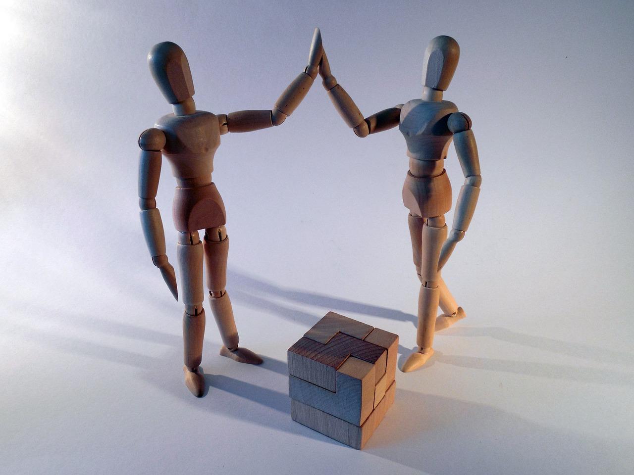 Zwei Figuren stehen vor dem gelösten Puzzle