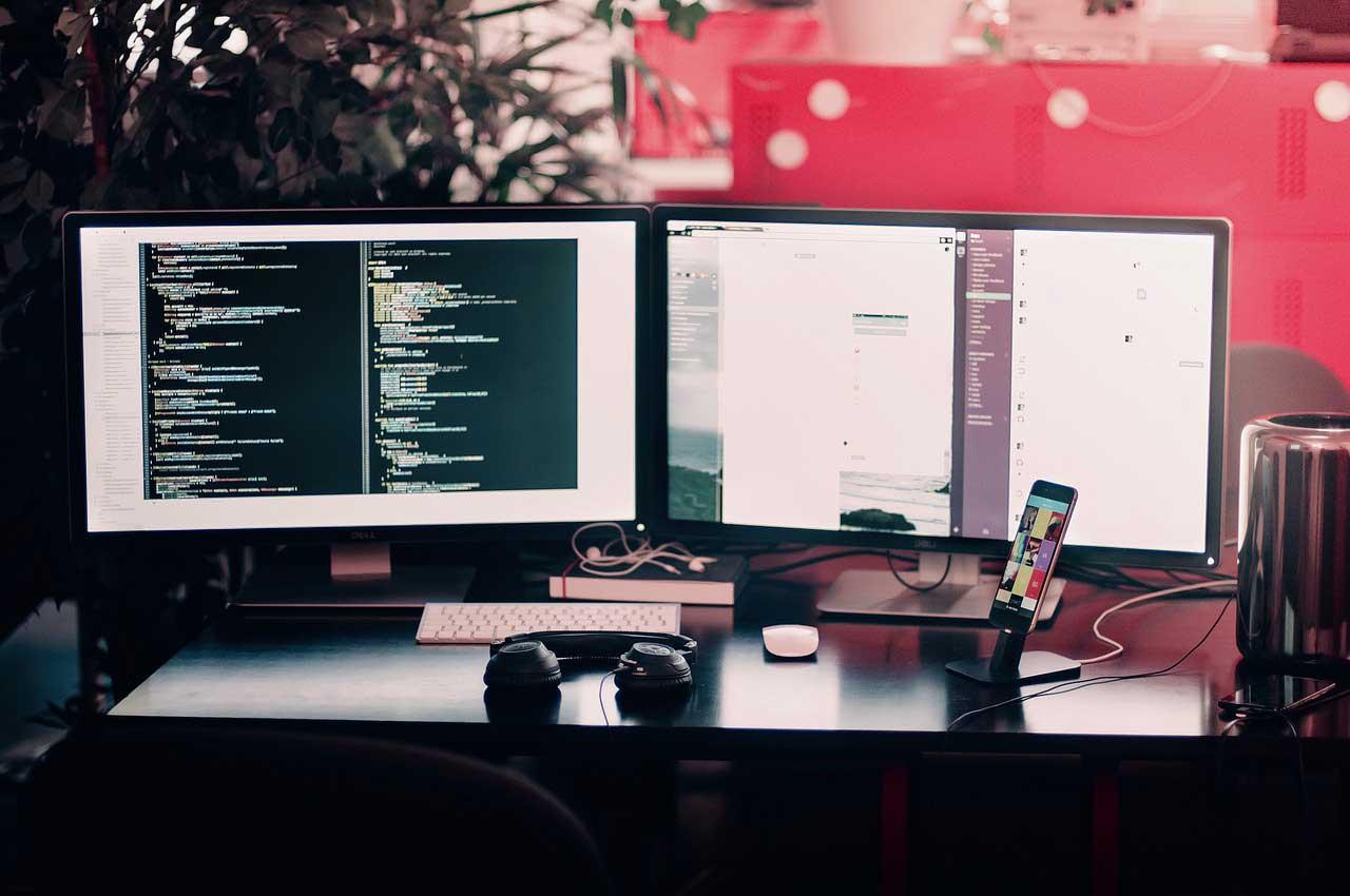 Schreibtisch mit zwei Monitoren, Kopfhörer und Smartphone