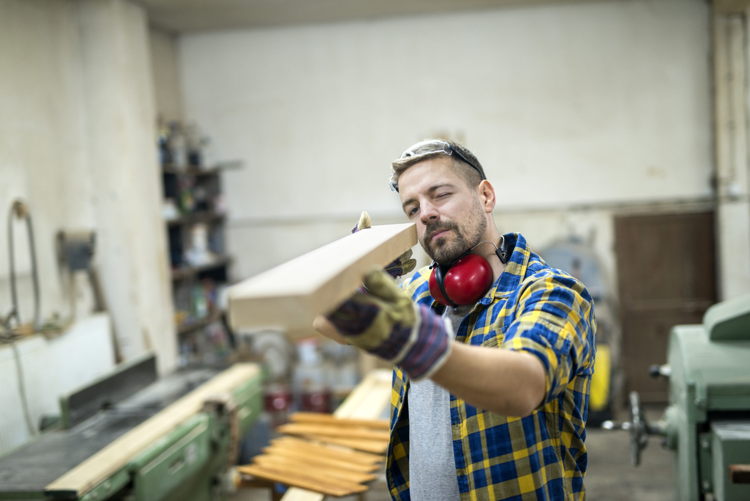 Carpenter checking quality of wood furniture part.